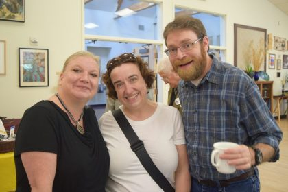 Three people smiling in Hanneman Hall