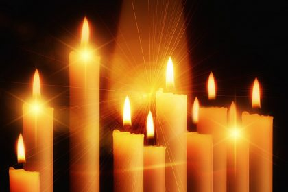ten lighted candles on dark background