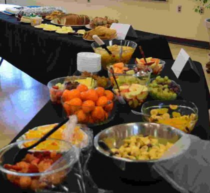 Fruit in bowls, breads and other foods arranged for a potluck