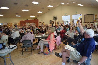 from side view -Congregation members at tables in fellowship hall holding up voting slips 2017-5-21