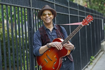 Guy Davis, smiling, holding a red guitar by a fence. African-American blues guitarist and more.