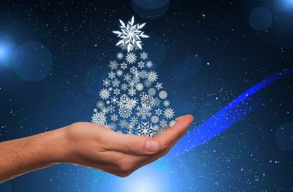 Hand holding small christmas tree made up of snowflakes on a blue background. 2017-11-09